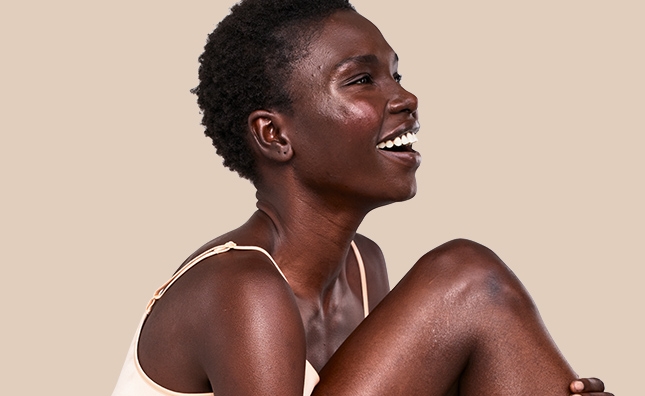 smiling woman with radiant skin on body and face from aveeno